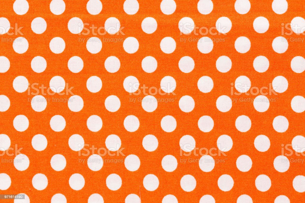 Close up of orange and white distressed polka dots background. Hi res