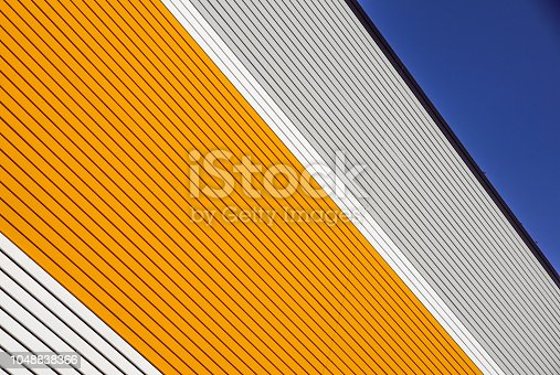 orange and white metal panel construction, wall of building with blue sky .