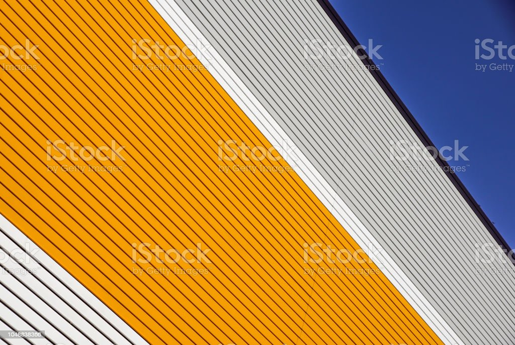 orange and white metal panel construction, wall of building with blue sky - foto stock