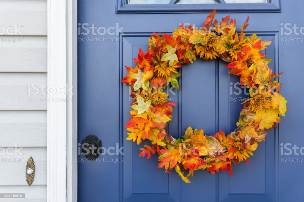 Orange and yellow autumn wreath on blue door stock photo