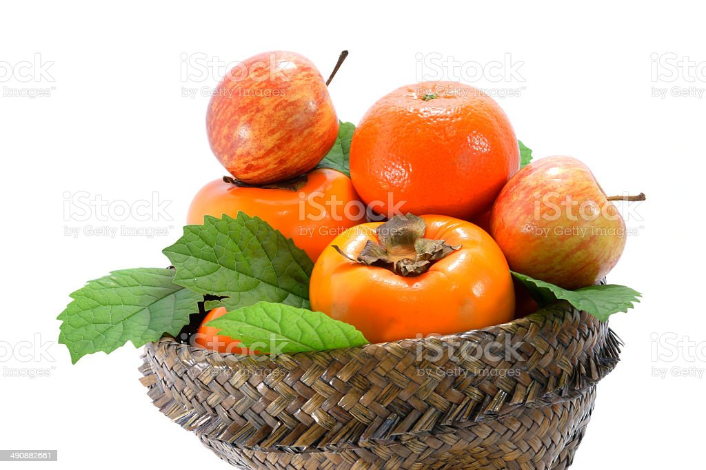 Orange, apple and persimmon in the basket of papyrus. stock photo