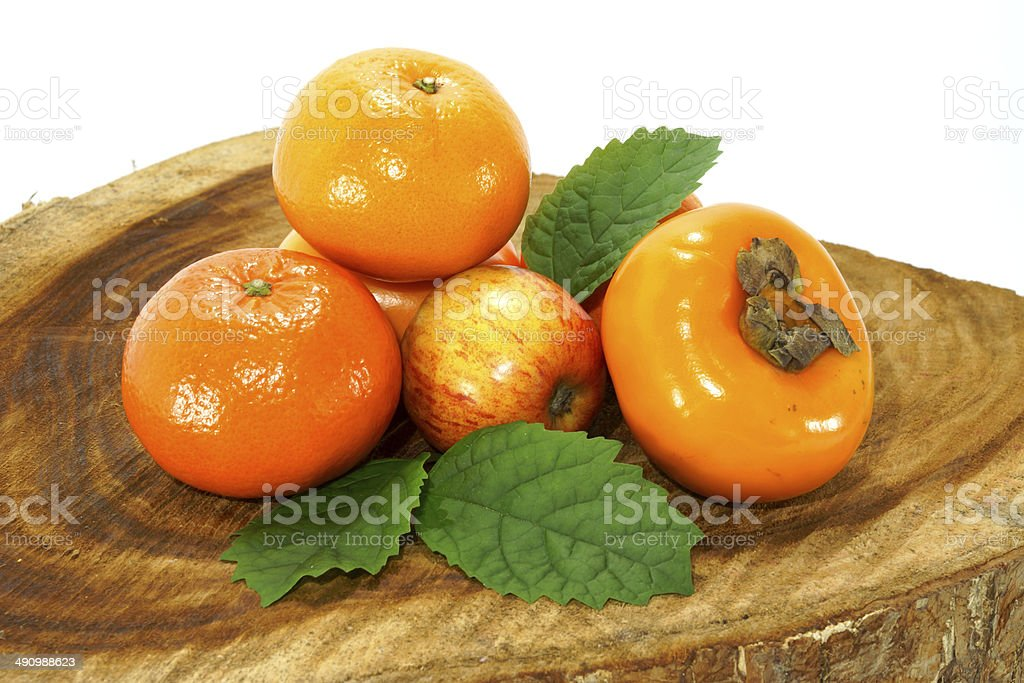 Orange, apple and persimmon on the wood stock photo