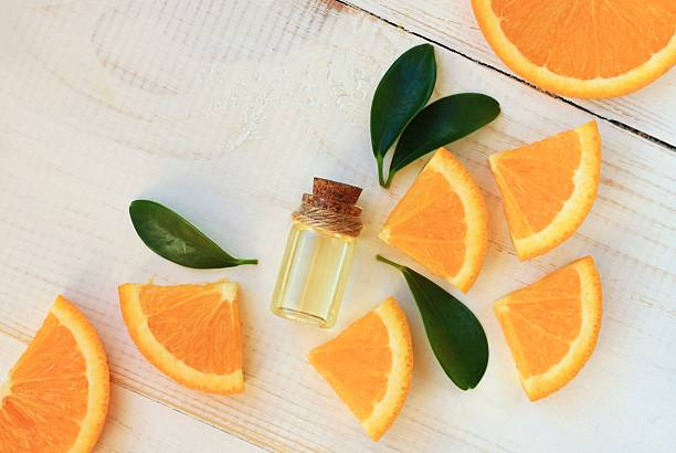 Orange aroma oil.  Bottle with essential oil, citrus scattered on wooden table. citrus fruit stock pictures, royalty-free photos & images