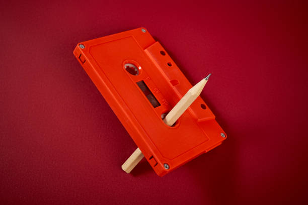 orange audio cassette and pencil on dark red background