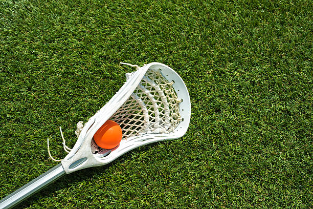 pomarańczowy i biały kij do gry w lacrosse piłka na sztucznej murawie - kij do gry w lacrosse zdjęcia i obrazy z banku zdjęć