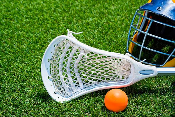 piłka pomarańczowy, biały kij do gry w lacrosse i hełm na sztucznej murawie - kij do gry w lacrosse zdjęcia i obrazy z banku zdjęć