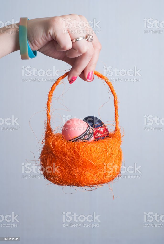 Orange basket with eggs in female hand, pink nail Polish, royalty-free stock photo