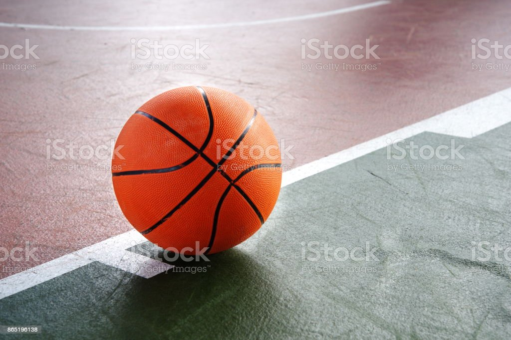 orange basketball for play on green brown court of gymnasium sport...