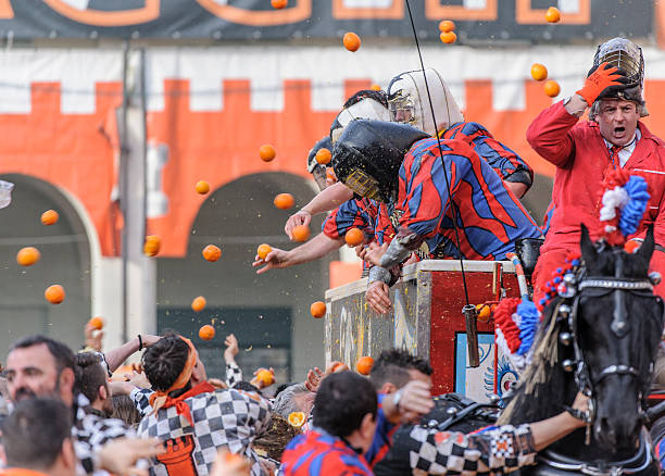 Orange Battle Ivrea, Italy - February 8, 2016: People (left) throw oranges against other people (right) dressed as medieval knight on a horse-drawn cart during the Battle of the Oranges that takes place every year during the Ivrea Carnival. During Orange Battle people re-enact a medieval rebellion when townsfolk of Ivrea fought versus the king. These days people are divided into teams: pedestrian teams and teams on a horse-drawn cart fight each other using oranges as weapons. working animal stock pictures, royalty-free photos & images
