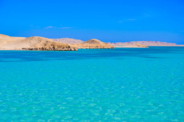 Orange Bay Beach with crystal clear azure water and white beach -  hammock in the water for relaxing - paradise coastline of Giftun island, Mahmya, Hurghada, Red Sea, Egypt.