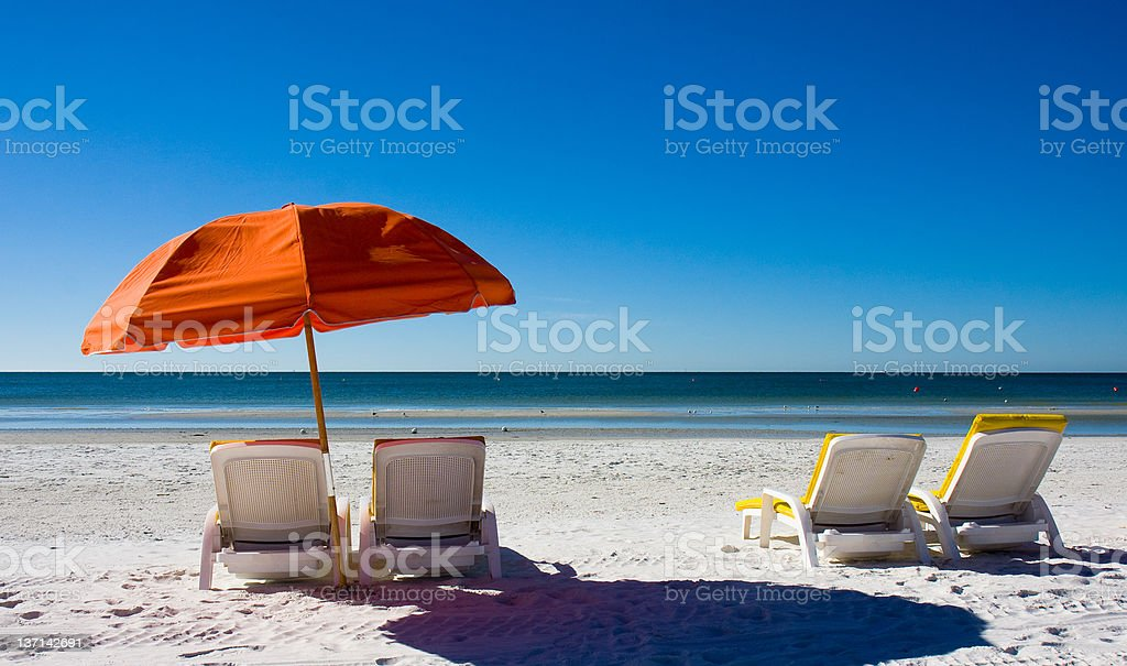 Orange beach umbrella and empty lounge chairs facing the sea stock photo