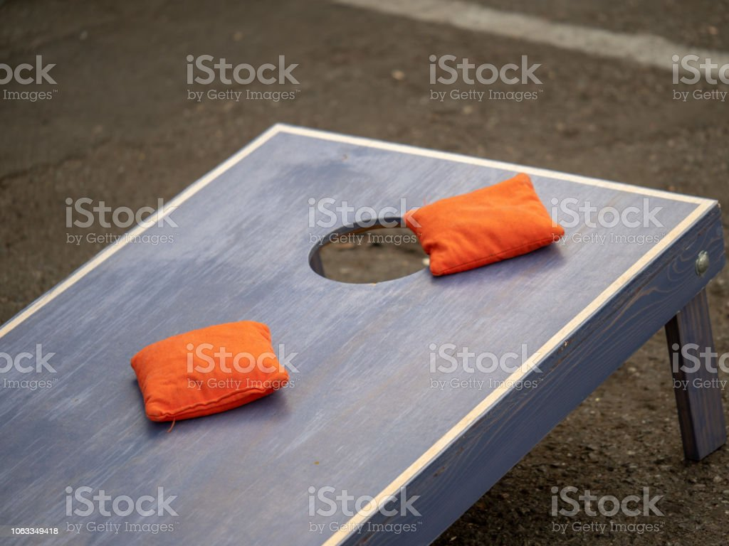 Orange beanbags sitting on blue cornhole board platform stock photo