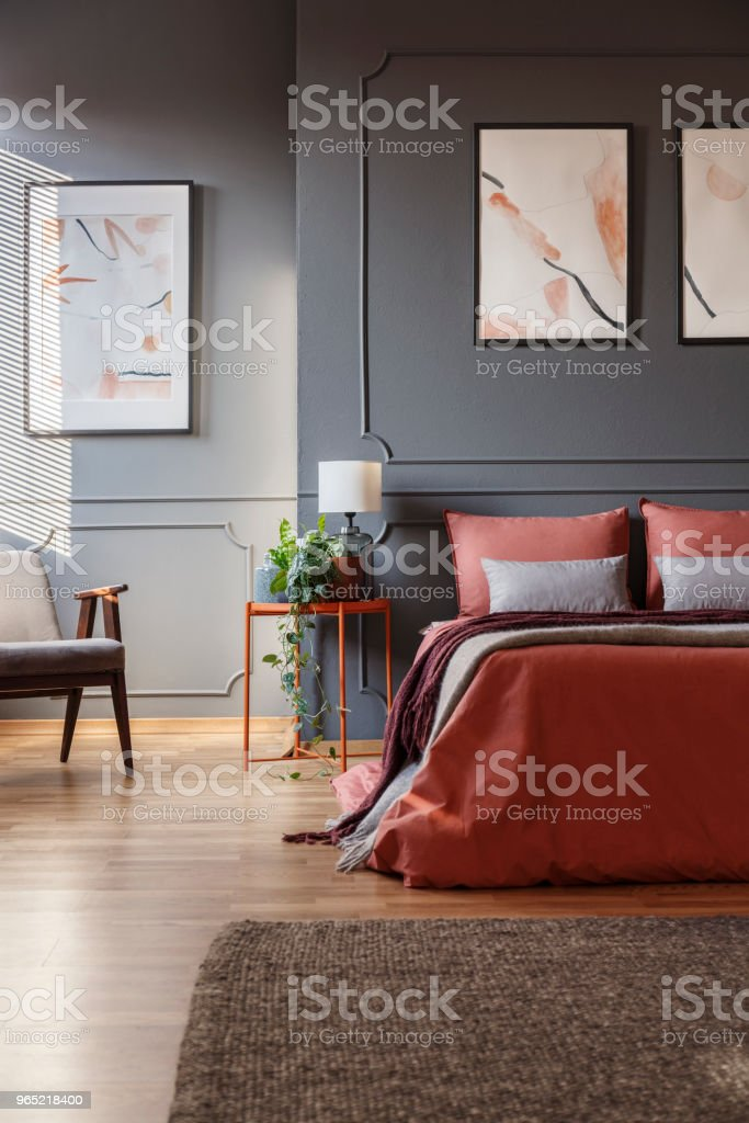 Orange bed against dark wall with molding and white posters next to a metal bedside table with a lamp on it in bedroom interior. Real photo royalty-free stock photo