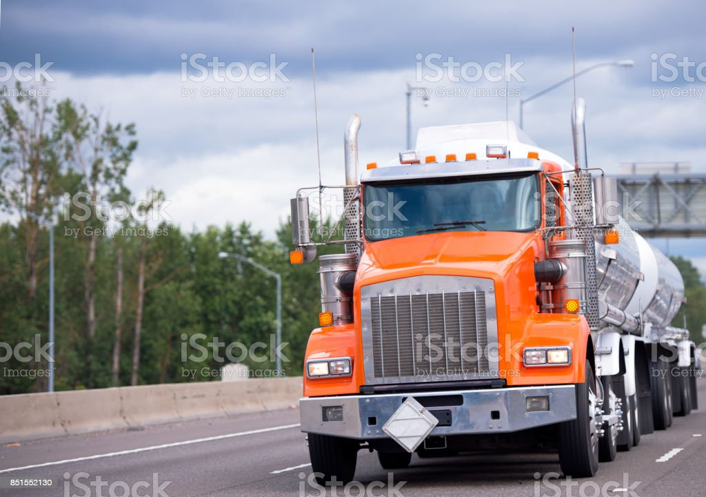 Orange big rig semi truck tractor with two tank trailers transporting fuel on the highway road stock photo