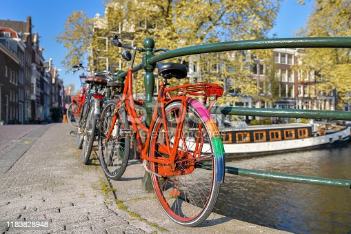 Orange bicycle with LGBT flag parked on a bridge in Amsterdam, Netherlands
