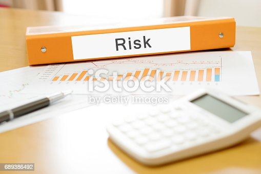 istock Orange  binder debtor on desk in the office with calculator and pen 689386492