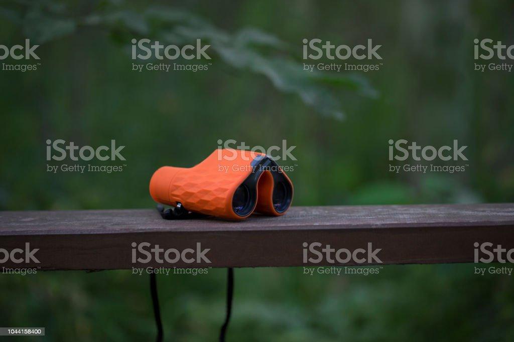 Orange binoculars on a wooden shelf stock photo