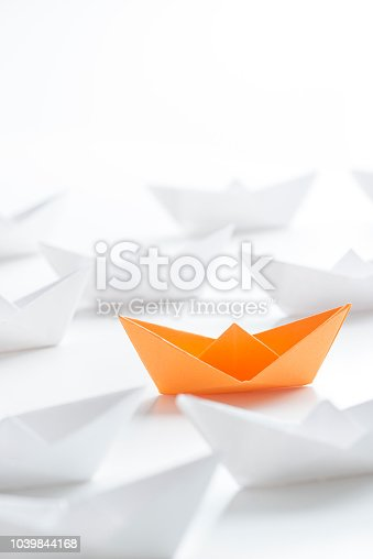 Orange paper boat among many white paper boats on white background.