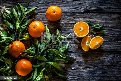 Top view of an orange branch with orange fruits shot on rustic wooden table. An orange is cut in halves. Predominant colors are green and orange. Low key DSRL studio photo taken with Canon EOS 5D Mk II and Canon EF 70-200mm f/2.8L IS II USM Telephoto Zoom Lens