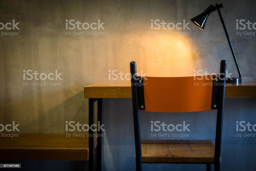 Orange brown chair and table in room with yellow light from lamp and cement wall in the background , dark tone stock photo