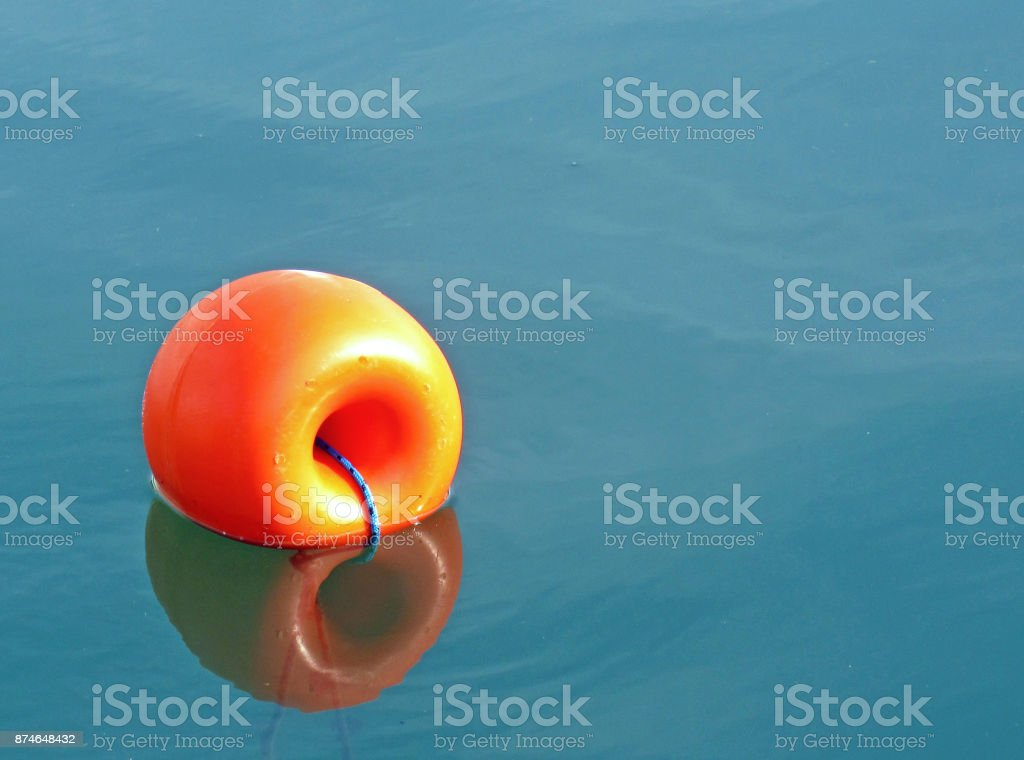 Orange buoy floating in the port stock photo