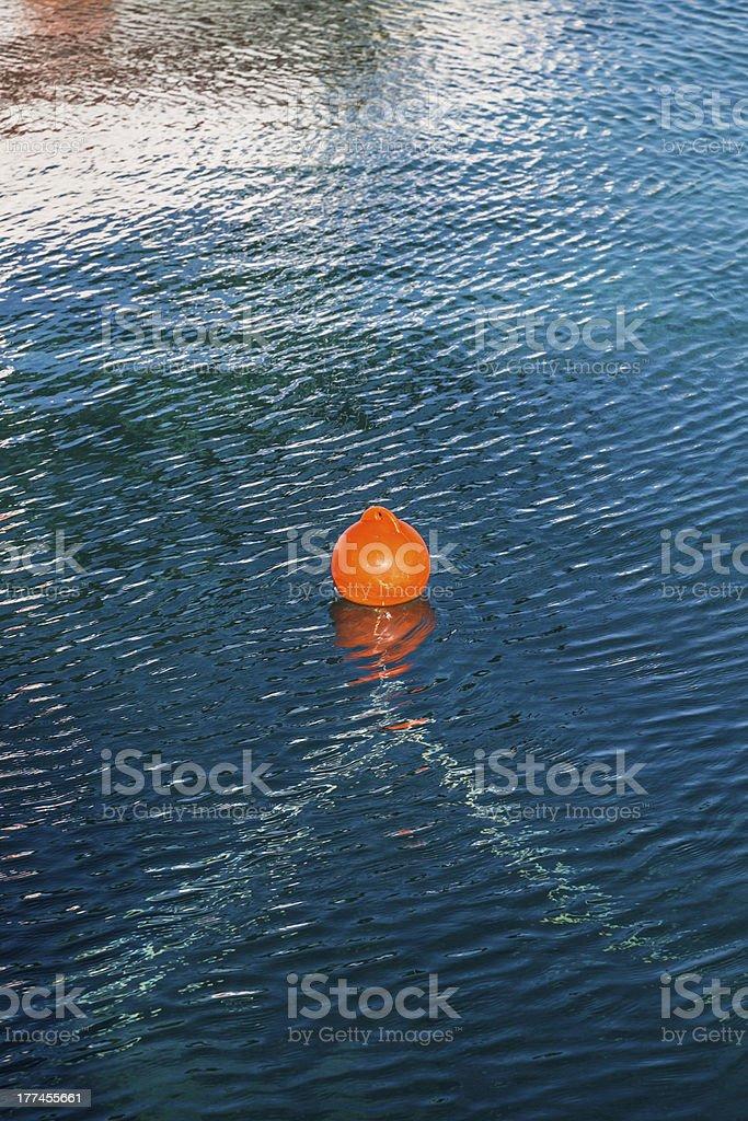 orange buoy in blue ocean water royalty-free stock photo