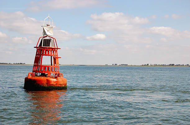 Orange buoy in the Eastern Scheldt,Zeeland,the Netherlands Buoy marking the navigable depth in the East Scheldt,the Netherlands. buoy stock pictures, royalty-free photos & images