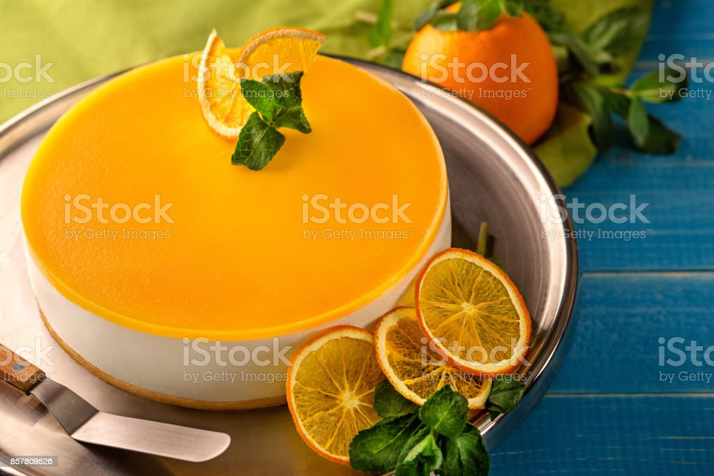 Orange Cake in white dish on the blue wood table stock photo