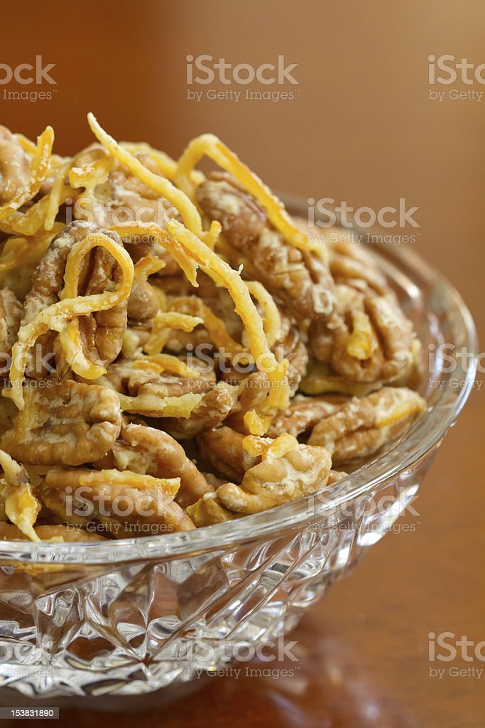 orange candied pecans on a cherry wood background royalty-free stock photo