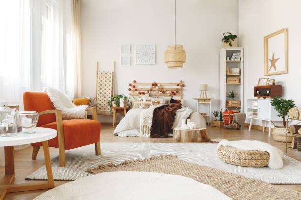 orangefarbene stuhl im schlafzimmer - fensterdeko herbst stock-fotos und bilder