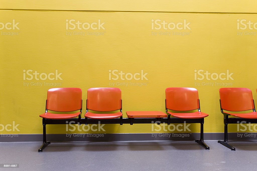 Orange chairs against a yellow wall royalty-free stock photo