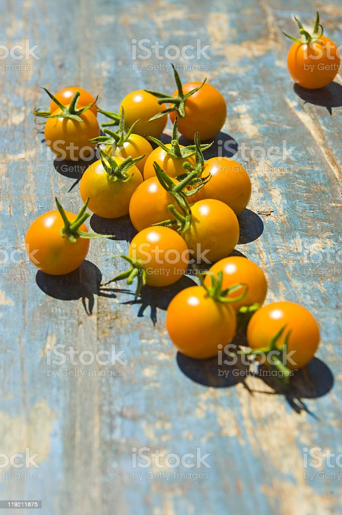 Orange cherry tomatoes on a rustic table stock photo