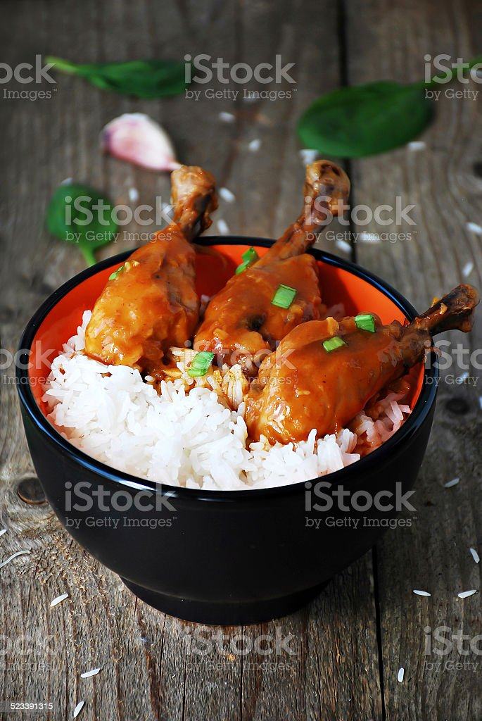Orange chicken thighs with basmati rice in bowl stock photo