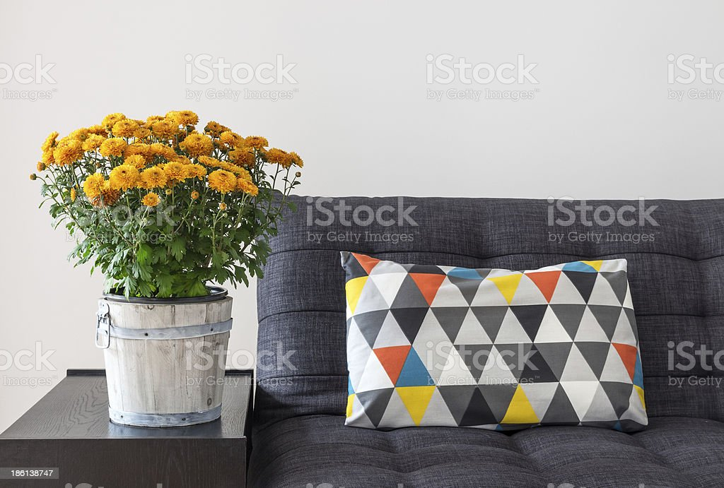 Orange chrysanthemums and bright cushion on a sofa