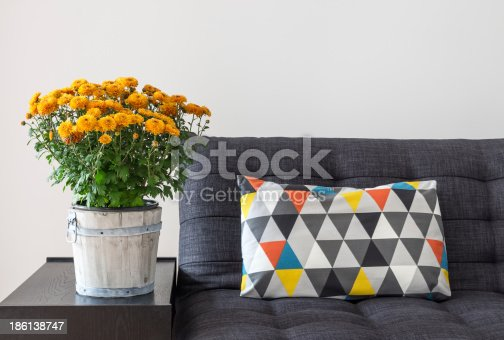 Bright cushion on a sofa, and orange chrysanthemums on a side table.