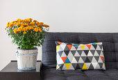 Orange chrysanthemums and bright cushion on a sofa