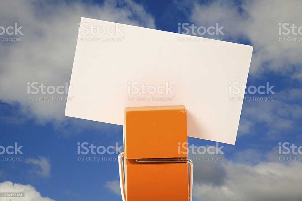 orange clothes pin holding a note with cloudy sky background stock photo