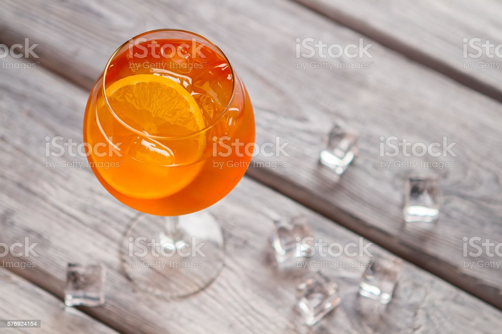 Orange cocktail in wineglass.