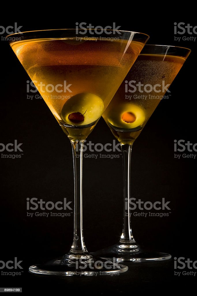 Orange Cocktails and Olives in Martini Glasses on Black Background royalty-free stock photo