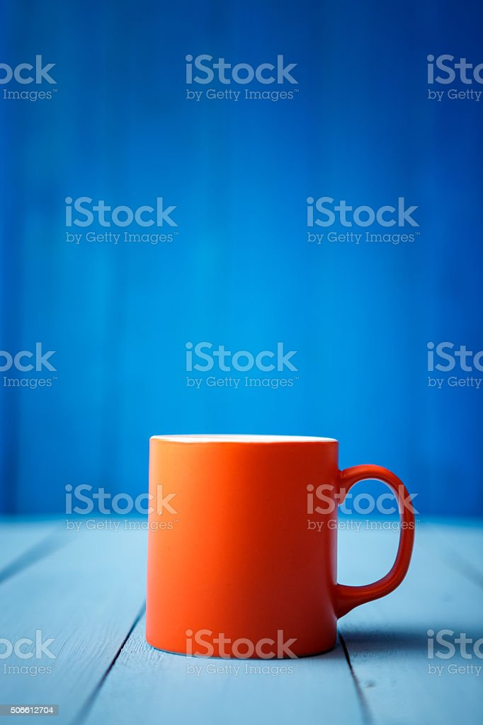 Orange coffee cup on blue wood stock photo