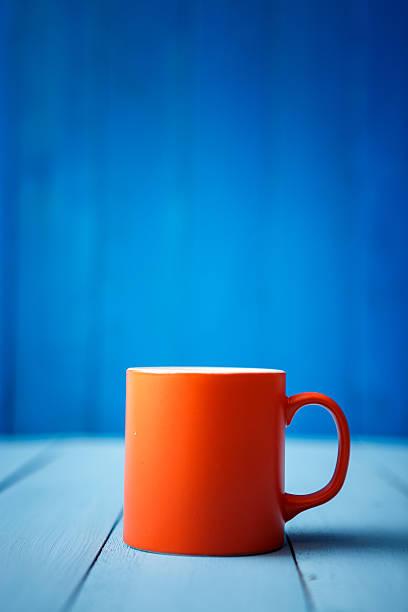 Orange coffee cup on blue wood stock photo