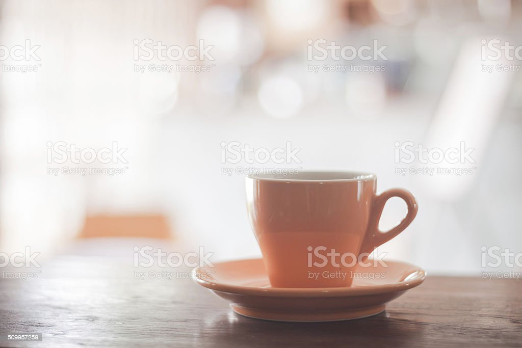 Orange coffee cup on wooden table stock photo