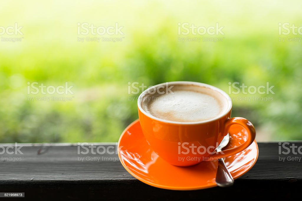 orange coffee cup with nature bokeh background. stock photo