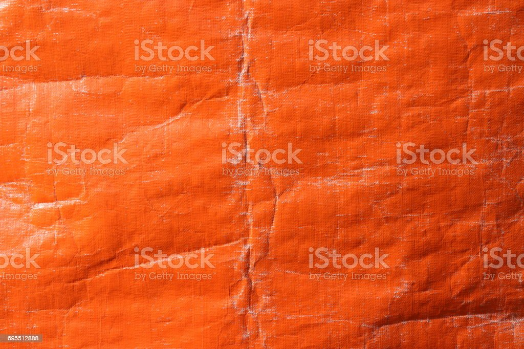 Orange color plastic tarpaulin covering, polyester fabric texture. stock photo