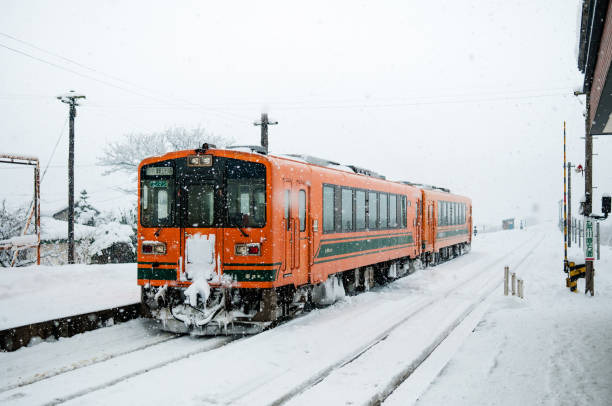 orange color train on snow covered tracks of tsugaru railway line in mid winter at goshogawara station, aomori, tohoku, japan. - goshogawara zdjęcia i obrazy z banku zdjęć