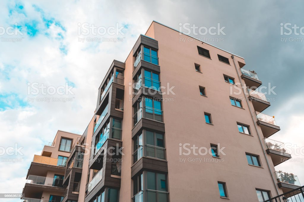 orange colored apartment house with glass balcony