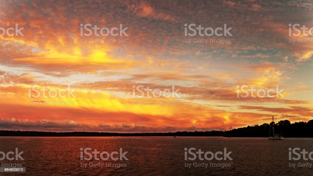 Orange colored cloudy saltwater lake sunset with water reflections Lake Macquarie Australia. stock photo