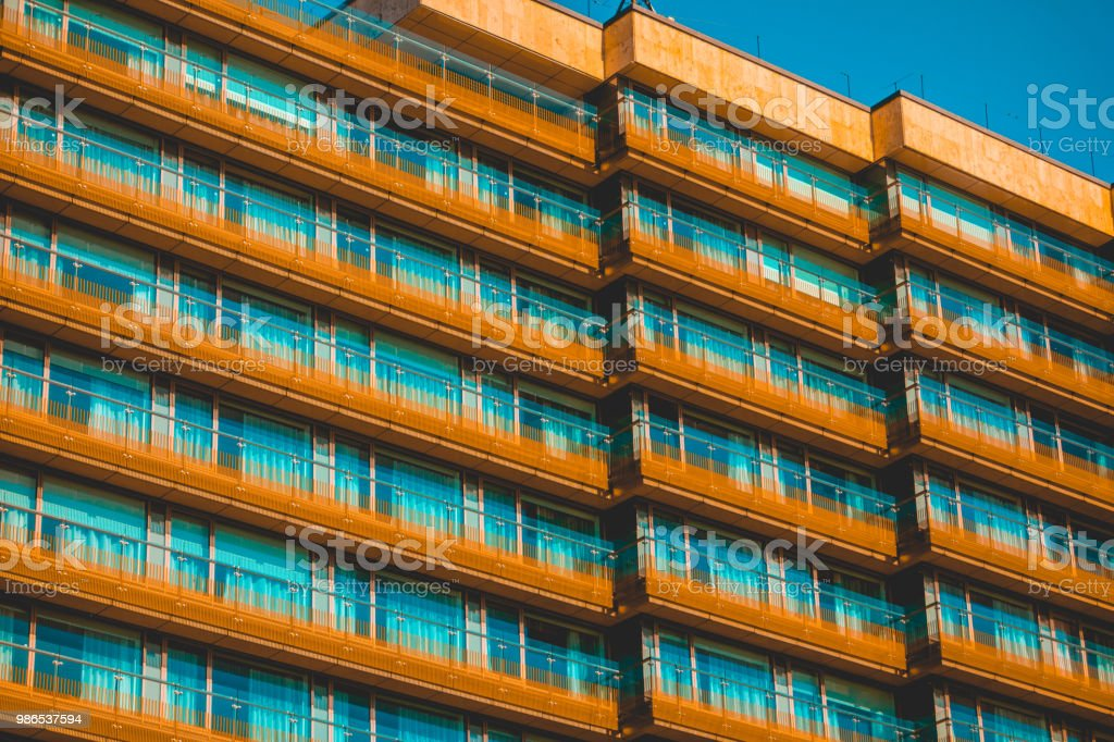 orange colored house with rows of glass balcony