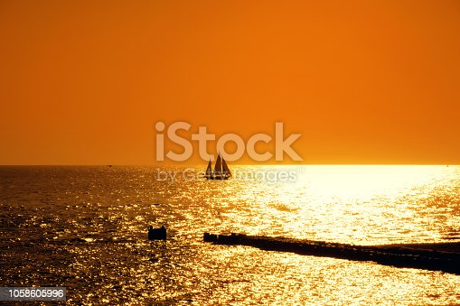 Orange colored seascape image with shiny sea and silhouetted sailboat over clear sky during sunset in Sarasota, Florida, USA