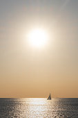 Orange colored seascape with sailboat over sunset sky